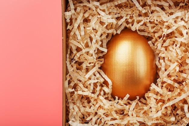 Złote jajko w pudełku na różowym tle. koncepcja wyłączności, najlepszego wyboru, nagrody, specjalnej niespodzianki, drogiego prezentu.