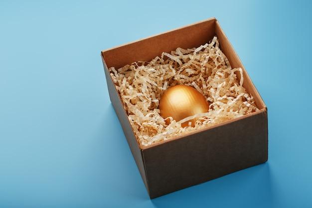 Złote jajko w pudełku z wiórami koncepcja indywidualności, ekskluzywności, najlepszego wyboru, nagrody, specjalnej niespodzianki, rzadkiego prezentu.