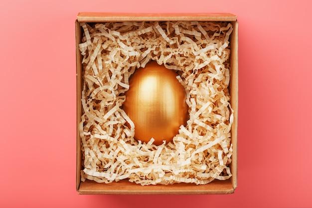 Złote jajko w pudełku z wiórami na różowym tle. pojęcie indywidualności, wyłączności, najlepszego wyboru, nagrody, specjalnej niespodzianki, rzadkiego prezentu.