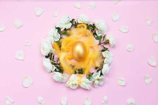 Złote jajko wielkanocne na gnieździe z białych róż i płatków.