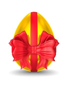 Złote jajko z czerwoną kokardą na białym tle