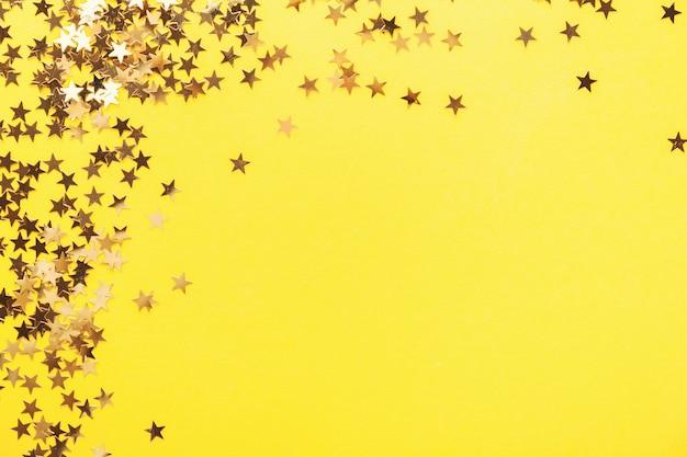 Złote jaśnienie gwiazd confetti na kolorze żółtym