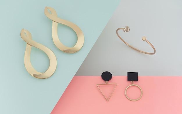 Złote kolczyki i bransoletka na pastelowym tle