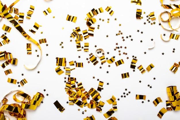 Złote konfetti na białej przestrzeni. pojęcie wakacji, imprezy, urodzin, dekoracji. transparent. widok płaski, widok z góry.