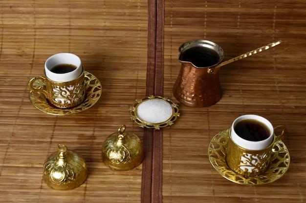 Złote kubki i turek na kawę na jasnym tle