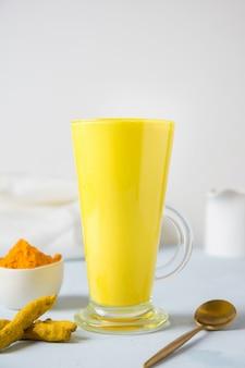 Złote kurkumowe mleko latte z korzeniem kurkumy