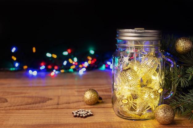 Złote lampki bożonarodzeniowe w słoiku mason na drewnianym stole na ciemnym tle, miejsca na tekst. obchody ferii zimowych
