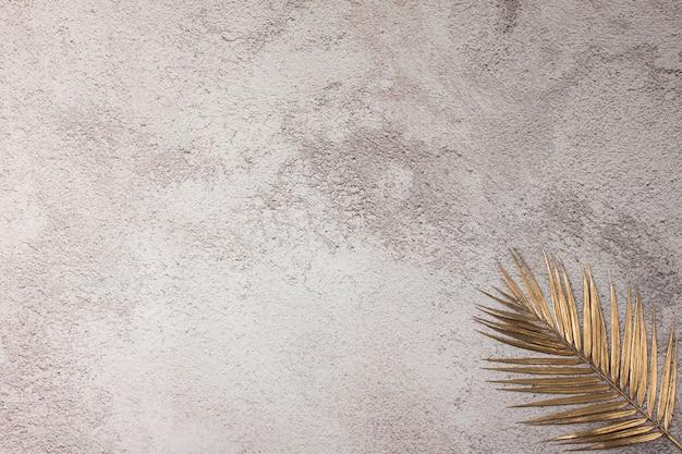 Złote liście na betonowej teksturowanej podłodze
