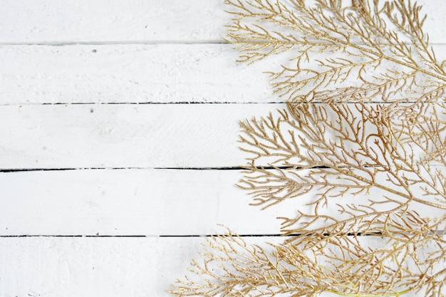 Złote liście na białym drewnie