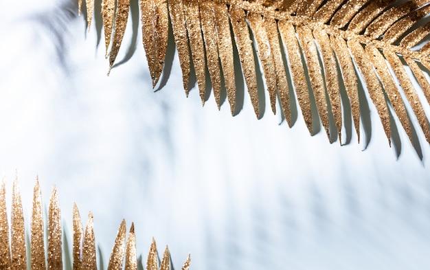 Złote liście palmowe i cienie na niebieskim tle ściany
