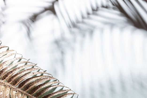 Złote liście palmowe i cienie na niebieskim tle ściany.