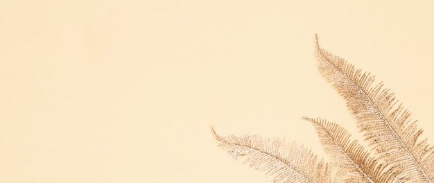 Złote liście palmowe na beżowym papierze