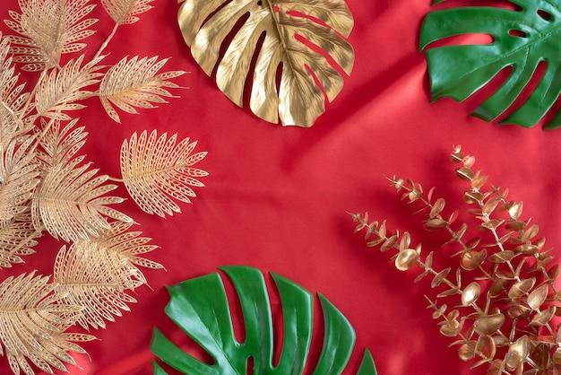 Złote liście roślin tropikalna monstera i ramka z wzorem palm na czerwonym tle top viewabstract