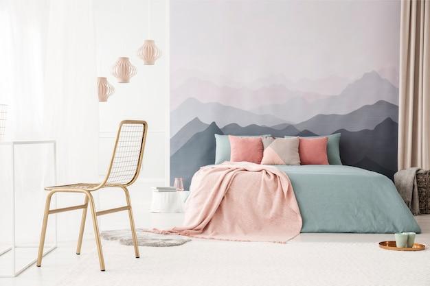 Złote metalowe krzesło w miękkim, jasnym wnętrzu sypialni z tapetą w góry pastelowy róż