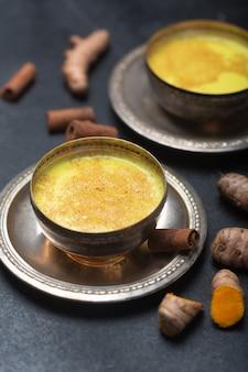 Złote mleko kurkumowe na czarnym stole ze składnikami