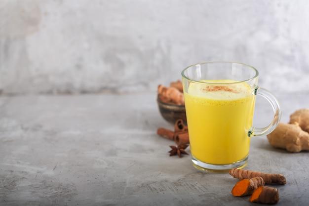 Złote mleko kurkumowe na szaro ze składnikami