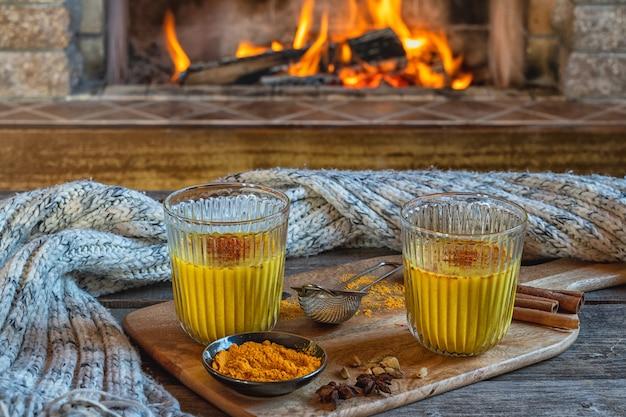 Złote mleko latte w dwóch szklankach z kurkumą i przyprawami przed kominkiem.
