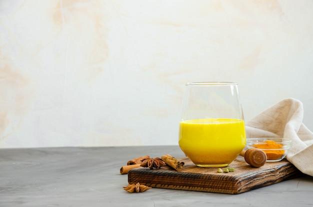 Złote mleko w szklance na desce z miodem i innymi przyprawami. zdrowy napój z mleka i kurkumy. orientacja pozioma. skopiuj miejsce.