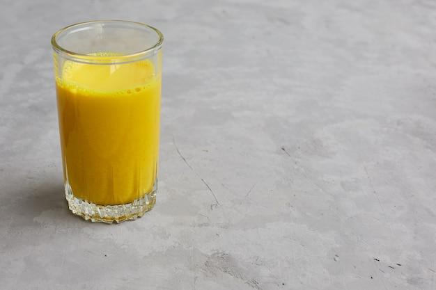 Złote mleko w szklance z dodatkami kurkumy i miodu.
