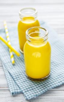 Złote mleko z cynamonem, kurkumą, imbirem i miodem na białej drewnianej powierzchni