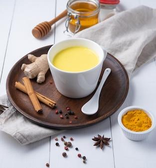 Złote mleko z kurkumą i cynamonem. dieta, zdrowy i detoksykacyjny napój. modny napój