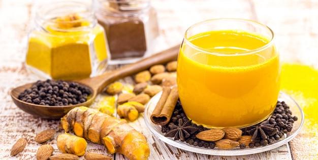 Złote mleko z kurkumą i innymi przyprawami, zdrowy napój szafranowy, cynamon, anyż, czarny pieprz i migdały