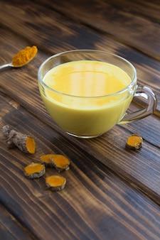Złote mleko z kurkumą w białej filiżance na drewnianym stole