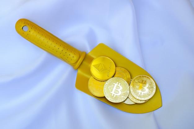 Złote monety bitcoin na złotej łopacie na białym tle