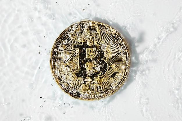 Złote monety bitcoin w koncepcji prania brudnych pieniędzy plusk wody na białym tle
