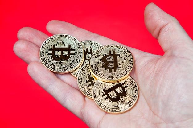 Złote monety elektronicznej kryptowaluty bitcoin, leżą w ludzkiej dłoni, zbliżenie, czerwone.