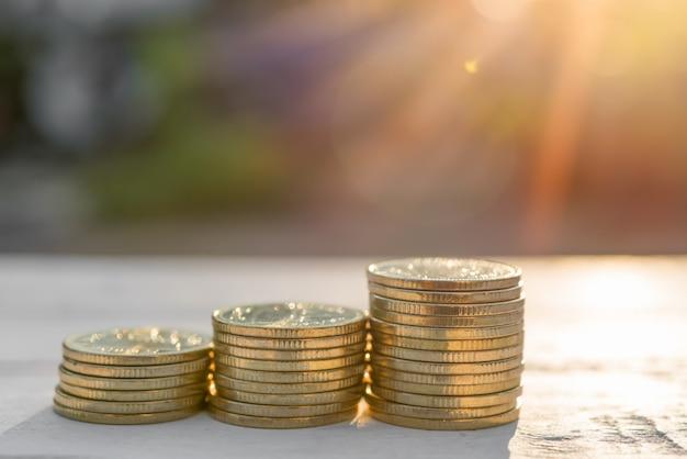 Złote monety na starym białym drewnianym stole