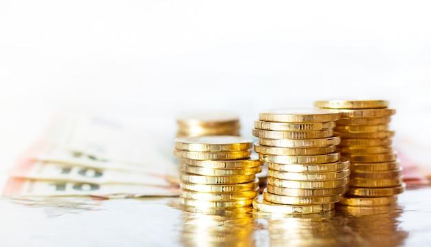 Złote monety piętrzyły się i rachunki euro na białym tle.