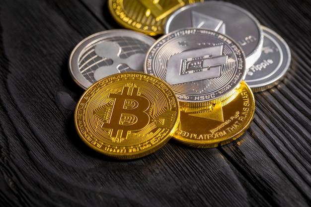 Złote monety z bitcoinem, na drewnie.