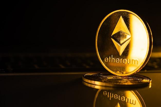 Złote monety z ethereum symbolem na komputerze.