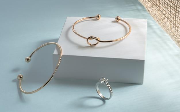Złote nowoczesne bransoletki i pierścionek z brylantem na białym i niebieskim tle w świetle słonecznym