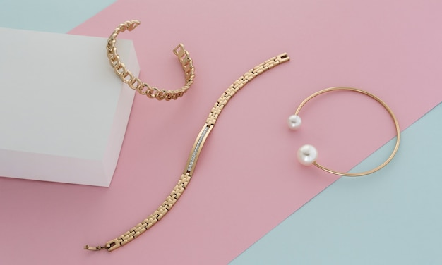 Złote nowoczesne bransoletki na pastelowych kolorach różowym niebieskim i białym tle papieru