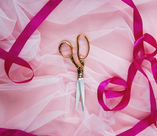 Złote nożyczki i wstążka na tle różowego tiulu. powyżej widok