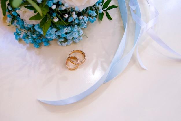 Złote obrączki i piękny bukiet ślubny z róż i błękitnej gipsówki w tle. szczegóły, tradycje weselne. zbliżenie