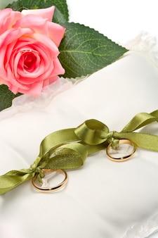Złote obrączki na białej poduszce z różą