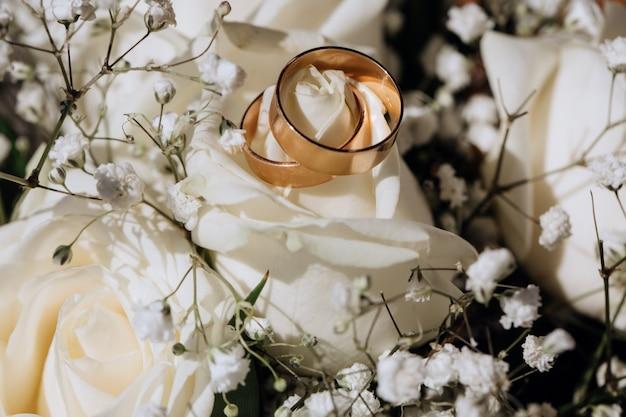 Złote obrączki na białej róży z bukietu ślubnego