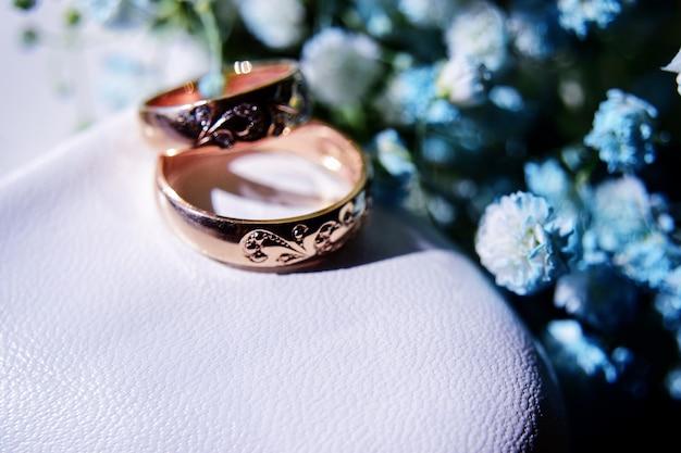 Złote obrączki na białym bucie panny młodej i piękny bukiet błękitnych łyszczec w tle. szczegóły, tradycje weselne. zbliżenie.