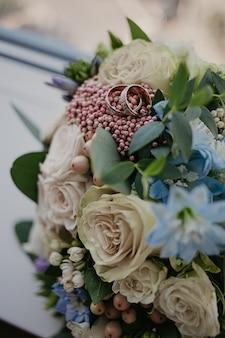 Złote obrączki na bukiet ślubny z pięknymi różami