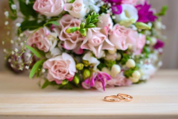 Złote obrączki ślubne i bukiet pięknych różowo-białych kwiatów róż na lekkim stole