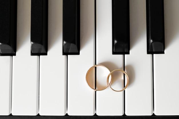 Złote obrączki ślubne leżą na klawiszach fortepianu