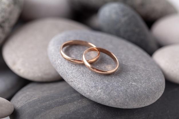Złote obrączki ślubne leżą na morskiej skale