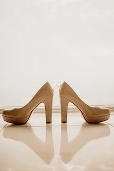 Złote obrączki ślubne między białymi butami na wysokim obcasie