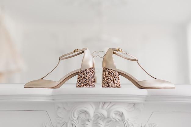 Złote obrączki ślubne między butami panny młodej