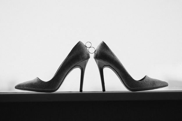 Złote obrączki ślubne między parą złotych butów na wysokim obcasie