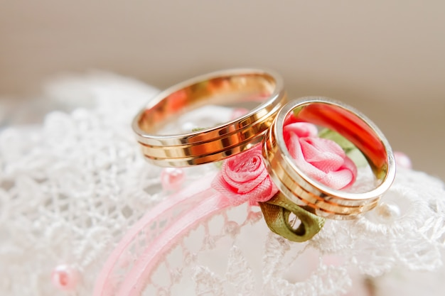 Złote obrączki ślubne na białej koronki