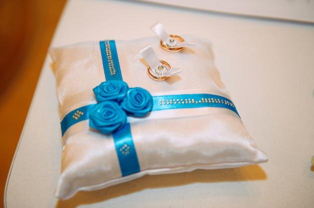 Złote obrączki ślubne na białej poduszce ozdobionej wstążkami i kwiatami, zbliżenie. motyw ślubny, akcesoria dla nowożeńców.